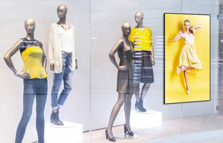 écran dans une vitrine entouré de mannequins