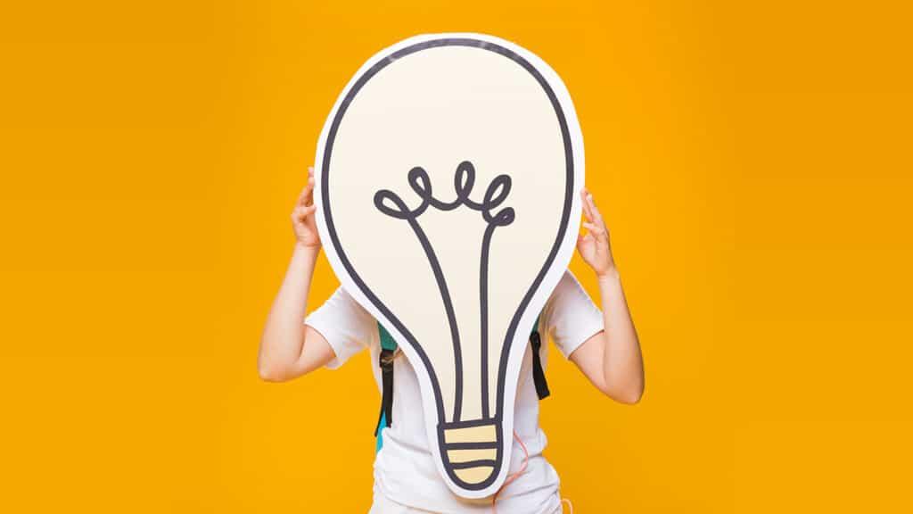 femme tenant un dessin d'ampoule